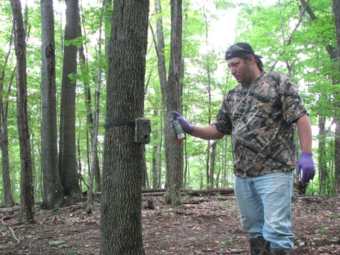 Hunting Guide Sam Zirkle makes sure no foreign scent remains on his Spypoint Camera and mount by spraying the area with