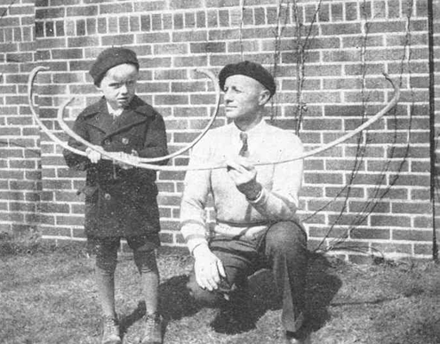 "Roy Case shows a young admirer a pair of hand-crafted bows. He made his own archery gear following Dr. Saxton Pope's suggestions in his classic book, ""Hunting With the Bow and Arrow."" Case also manufactured and sold broadheads from the 1920s until the early 1950s."