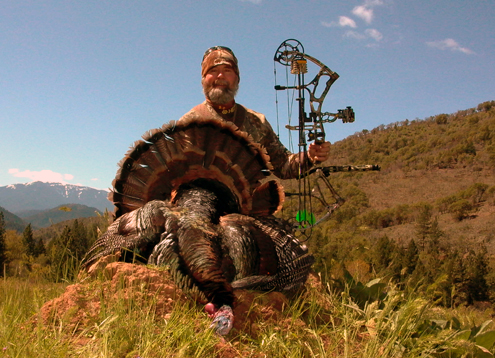 The author reaching the century mark. 100 turkeys taken with a bow.