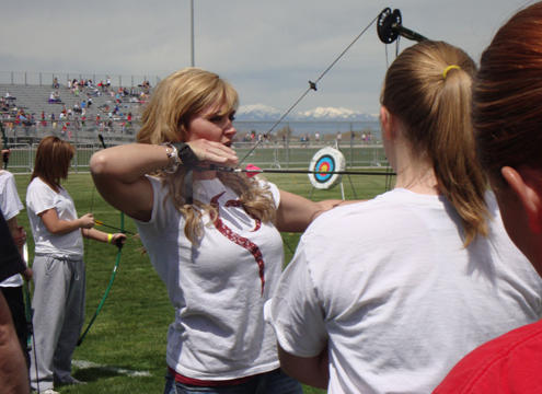 The author spending time instructing an archery class for young women.