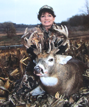 Longtime friend Brenda Valentine is pictured posing with a cornfed Iowa whitetail in the field where he dropped after her well-placed shot. Photos like these take only moments to set up and yet perfectly capture the moment where a hunter's smile says it all.