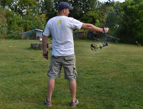 With the same straight stance, the shooter is holding the bow at the target, getting ready to lock on his release and begin the draw cycle.