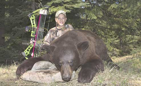 All smiles at a well-placed shot, young Easton poses with his redemption black bear.