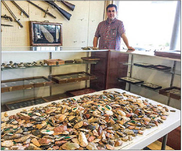 Brock Smith stands behind the counter of The Depot Antique Mall, which includes a section devoted to Native American artifacts such as a table full of arrowheads.