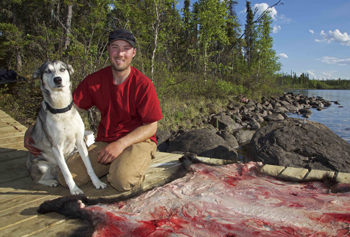 Outfitter Kobly Morrison of Bear Pro Safaris with his retired sled dog, Blue, after skinning Clay's bear.