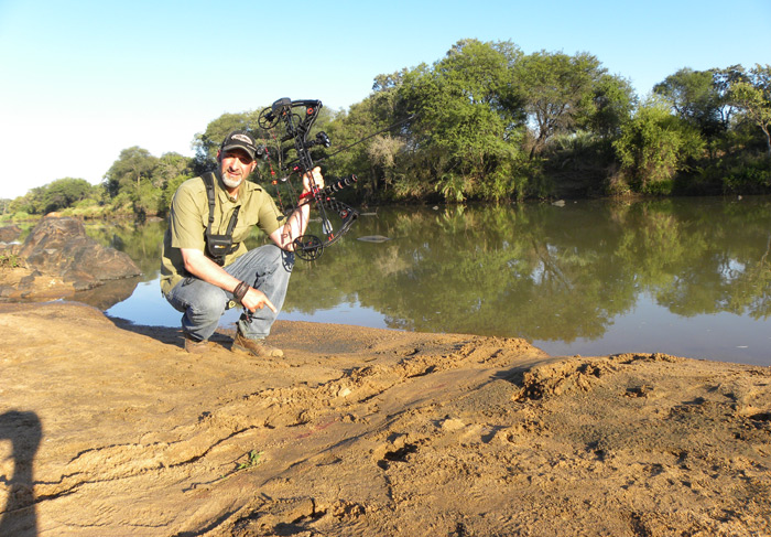 Author kneels in the sand, drag marks show the large croc was the one to take the bushbuck.
